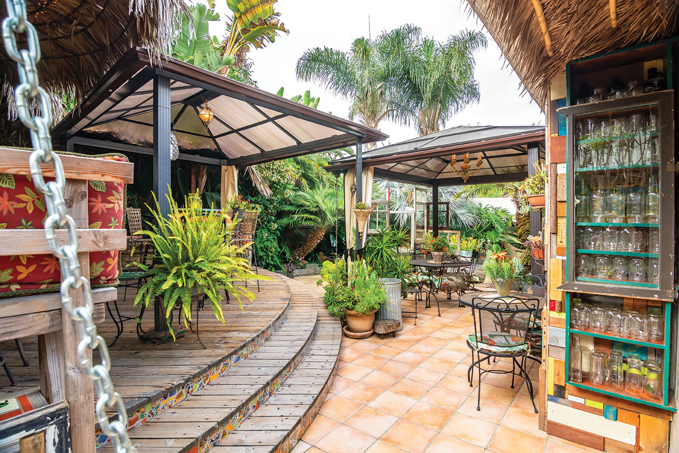 DIY gazebo kits and recycled upcycled bookcase with glasses in a changeable artistic garden in san diego
