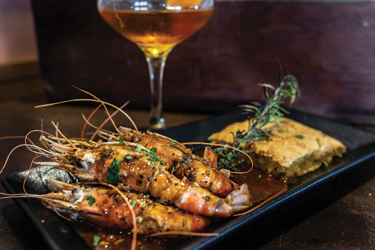 southern-style barbecue BBQ shrimp with sweet potato cornbread at North Park's Louisiana Purchase in San Diego with a New Orleans style cocktail in the background